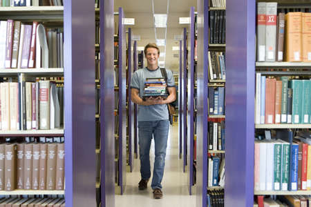 armful: Young man with armful of books in library, smiling, portrait