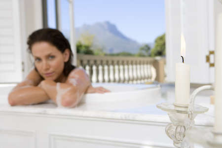 lavishly: Young woman in bath, portrait, focus on candle in foreground LANG_EVOIMAGES