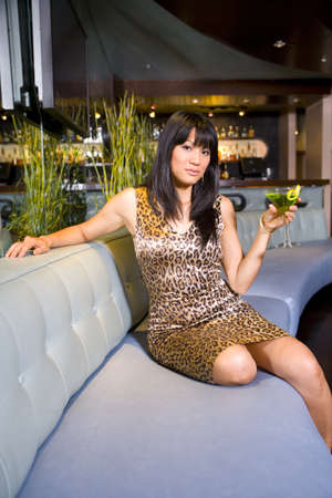 lavishly: Young woman with cocktail in bar, portrait