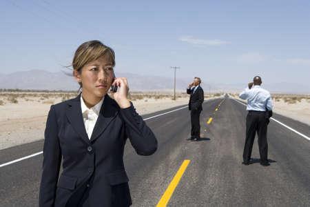 waistup: Los empresarios y mujer en medio de la carretera del desierto que usan tel�fonos m�viles