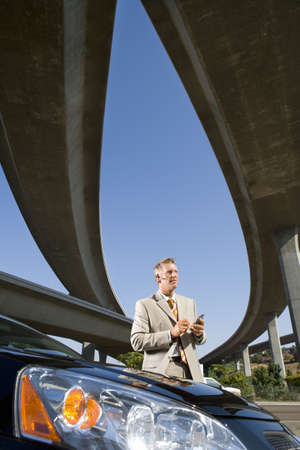 electronic organiser: Businessman using electronic organiser by car beneath overpasses, low angle view LANG_EVOIMAGES