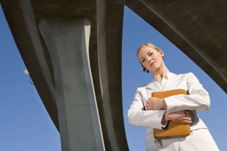 gals: Businesswoman holding folder beneath overpasses, low angle view LANG_EVOIMAGES