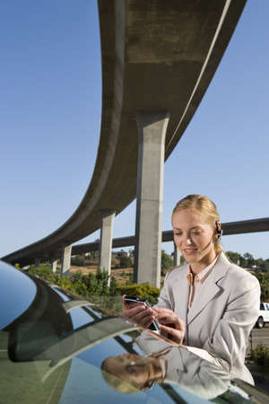 electronic organiser: Businesswoman with earpiece using electronic organiser by car beneath overpass