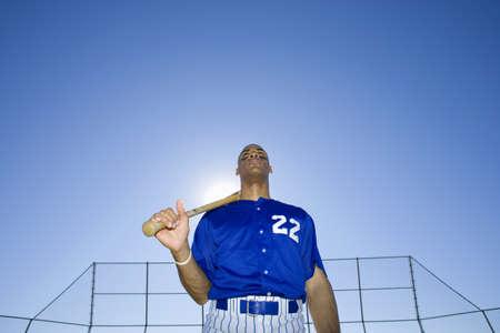 waistup: Bateador de b�isbol, con el dorsal � ? ~ 22� ? ? uniforme azul, de pie en terreno de juego con el bate que descansa sobre los hombros, vista frontal, retrato, vista de �ngulo bajo (retroiluminado) LANG_EVOIMAGES