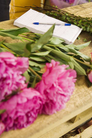 still lifes: Pink flowers on table beside order pad in flower shop, close-up (still life)