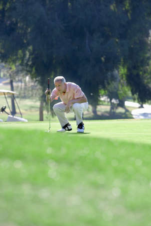 lining up: Mature man lining up putting shot on green in mid-distance, holding putter, crouching, focus on background
