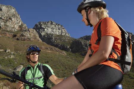 waistup: Pareja en bicicleta de monta�a en el valle, que se sienta en bicicletas, tomar descanso, vista de �ngulo bajo LANG_EVOIMAGES