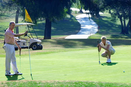 lining up: Mature couple playing golf, woman lining up golf shot on putting green, man holding flag LANG_EVOIMAGES