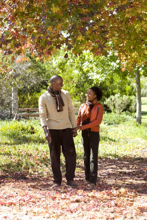 appreciating: Couple walking in autumn park, holding hands, smiling LANG_EVOIMAGES