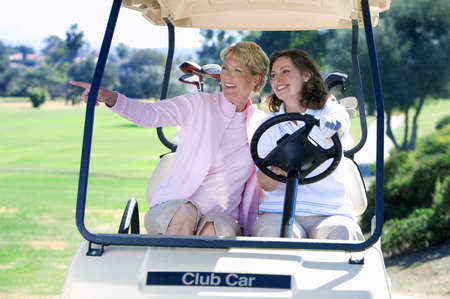 appreciating: Two mature women sitting in golf buggy on golf course, brunette driving, blonde pointing, smiling, front view