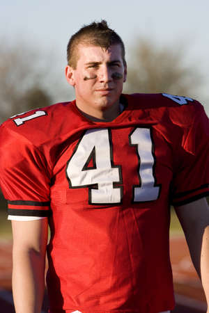 waistup: American football player wearing red football strip with number '41', standing on pitch, front view