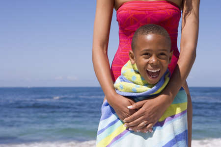 appreciating: Mother and son (5-7) standing on beach, boy wrapped in striped towel, smiling, front view, portrait
