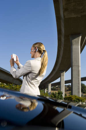 electronic organiser: Businesswoman using electronic organiser by car beneath overpass, low angle view
