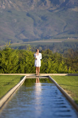 western european ethnicity: Young woman wearing white bath robe, standing outdoors by pool LANG_EVOIMAGES
