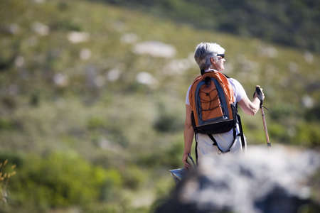 Mature woman hiking on mountain trail, carrying rucksack and using hiking pole, rear view LANG_EVOIMAGES