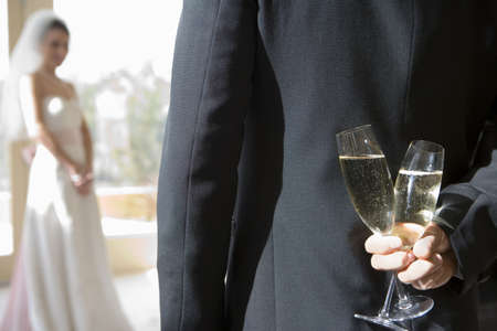 lavishly: Groom holding two champagne flutes behind back, bride standing in background, focus on groom in foreground, rear view