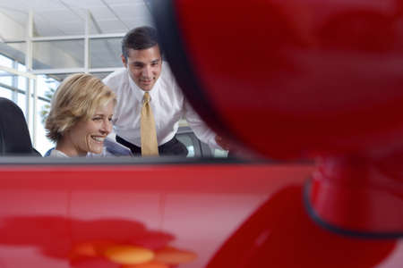 lavishly: Woman sitting in red convertible car in showroom, salesman assisting, side view, focus on background