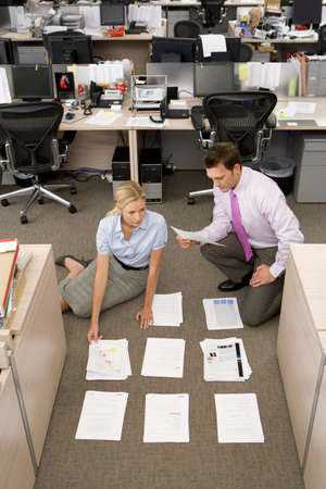 organising: Businessman and woman organising paperwork into piles on floor, elevated view