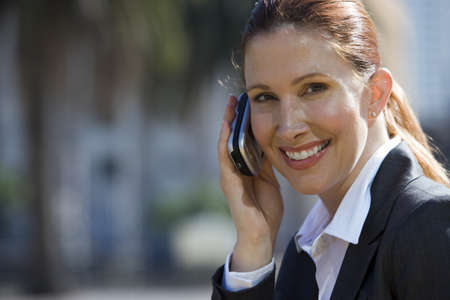 toils: Businesswoman using mobile phone, outdoors, smiling, side view, portrait LANG_EVOIMAGES