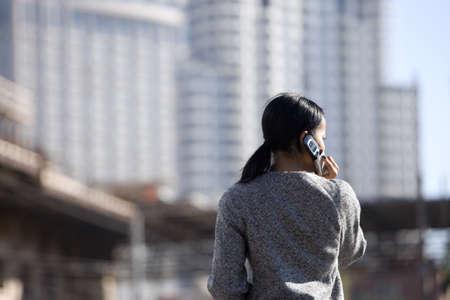 waistup: Empresaria que usa el tel�fono m�vil, al aire libre, vista trasera