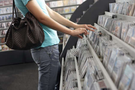 record shop: Young woman sifting through CDs in record shop, side view, mid-section LANG_EVOIMAGES