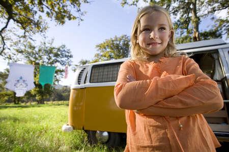 waistup: Girl (9-11) con los brazos cruzados por autocaravana en el campo, sonriendo, vista de �ngulo bajo