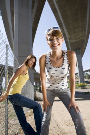 western european ethnicity: Young woman beneath overpasses, friend by fence, smiling, portrait, low angle view LANG_EVOIMAGES