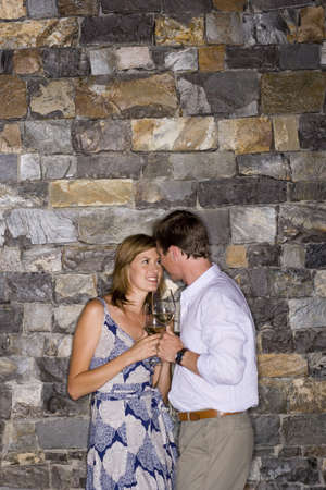 leant: Couple flirting beside stone wall, holding glasses of white wine, smiling