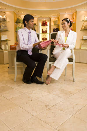 lavishly: Young woman sitting on chair in glamorous boutique, male shop assistant showing her pink designer handbag, smiling