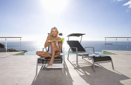 lavishly: Young woman with celery on sun bed by infinity pool and sea, portrait, low angle view (lens flare)