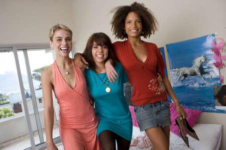 western european ethnicity: Three teenage girls (15-17) standing on bed in bedroom, smiling, portrait LANG_EVOIMAGES