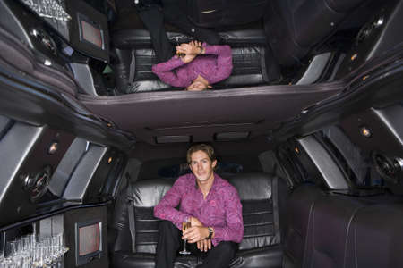 lavishly: Young man with drink in limousine, reflection in ceiling, smiling, portrait
