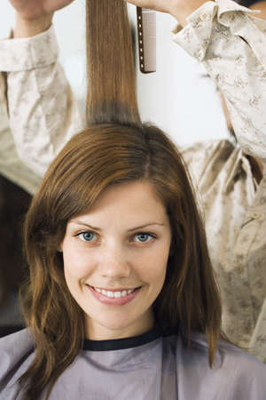 waistup: Hairdresser cutting womans hair in salon, smiling, front view, close-up, portrait