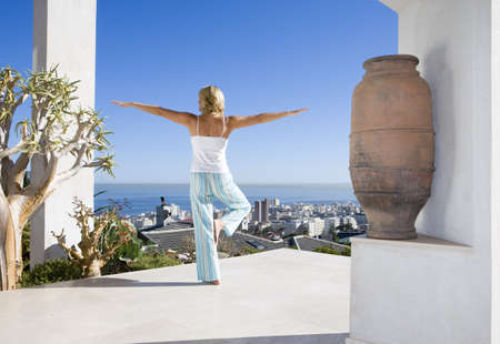 lavishly: Young woman standing on balcony in tree pose yoga stance, rear view LANG_EVOIMAGES