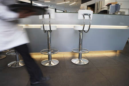 gentleman s: Waiter walking through cafe bar, carrying tray, side view (blurred motion)