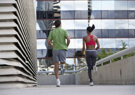elevated walkway: Couple jogging on urban elevated walkway, running side by side, rear view, surface level