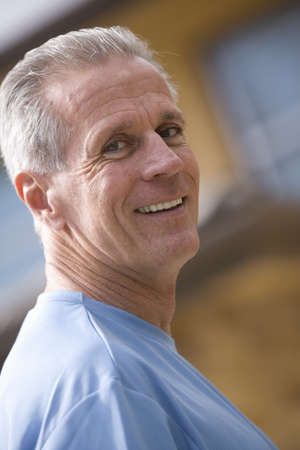 leant: Senior man wearing blue t-shirt, smiling, close-up, side view, portrait (tilt)