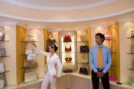 lavishly: Male shop assistant watching woman shopping for designer handbags in glamorous boutique