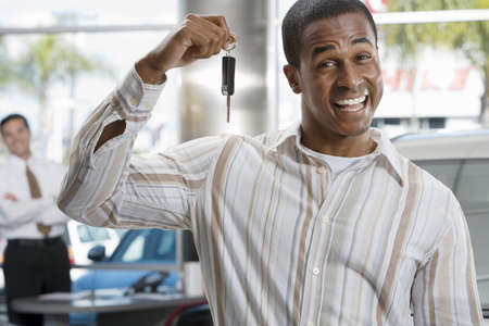wor: Salesman in car showroom, focus on male customer holding key in foreground, smiling, portrait LANG_EVOIMAGES