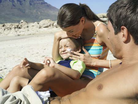 gentleman s: Family relaxing on beach, boy (4-6) sitting in mothers lap, woman applying suncream to sons face, side view LANG_EVOIMAGES