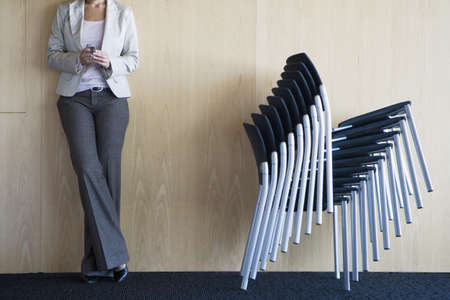 toils: Businesswoman standing in conference room beside stack of chairs, holding mobile phone, low section