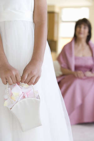 hold ups: Senior woman, in pink dress, looking at bridesmaid (8-10) holding wedding gift, focus on foreground