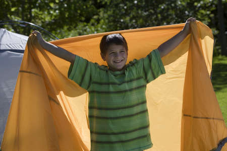 waistup: Boy (8-10) assembling dome tent on garden lawn, holding orange outer tent canvas behind back, arms up, smiling, portrait