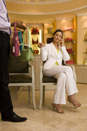 lavishly: Young woman sitting on chair in glamorous boutique, male shop assistant showing her selection of designer handbags, woman using mobile, pointing LANG_EVOIMAGES