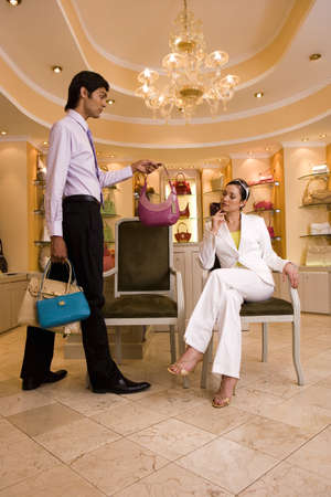 designer chair: Young woman sitting on chair in glamorous boutique, male shop assistant showing her selection of designer handbags
