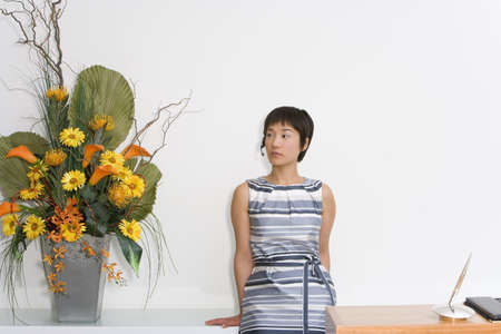gals: Young female receptionist by desk looking at flower arrangement LANG_EVOIMAGES