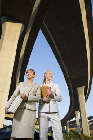 relishing: Two businesswomen with briefcase and folder beneath overpasses, low angle view LANG_EVOIMAGES