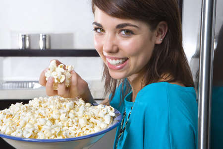 cau: Young woman standing by fridge with bowl of popcorn, smiling, portrait, close-up