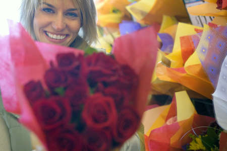 shop display: Woman holding large bouquet of red roses beside shop display in florists, smiling, close-up, portrait LANG_EVOIMAGES