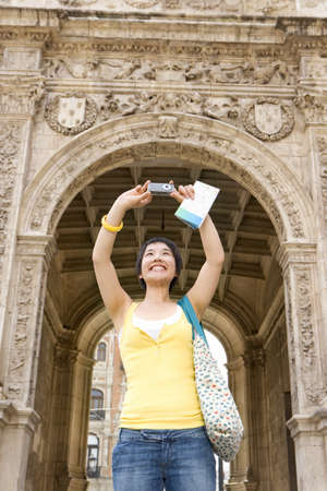 gratifying: Young female tourist taking photograph by archway, low angle view